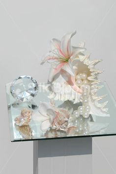 3 piece sea shell floral displays with pearls ideal for your home. Fresh Touch stargazer seashell display with large ivory pearls.	 Modern seashell display, amazing quality and ultra realistic.	 Flowers and pearls come assembled on a set of 3 seashells.	 Floral display perfect for side tables or table centrepieces.	 Fantastic modern peach and ivory shell display. Flowers can be changed to any desired colour or species. Main shell measures approximately 12cm wide; 17cm long; 13cm tall.