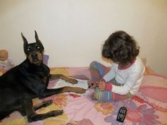 """Baby girl giving her doberman a """"pawdicure."""""""