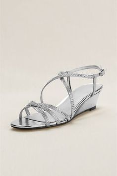 The super strappy wedge is the perfect sandal for every occasion! Satin wedge sandal features glistening embellishments across each strap. Heel Height - 1 3/4 inch. Available in Champagne and Silver. Imported.