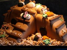 Sponge cake carved to look like climbing frame covered with fondant . Decorated with fondant hamsters with vegetables . for the sawdust i mixed white and brown fondant and grated it to get the small pieces