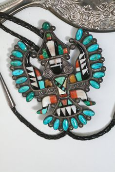 Zuni Turquoise Bolo Pendant LARGE Knife Wing (knifewing) Dancer unisex mens or womens icon old pawn native american made necktie or pendant. Best example we have seen!! Stones include several different colors of turquoise, spiny oyster, onyx, mother of pearl, two stones that look like mastodon bone, a red stone (inlay on the feet) and a brown stone with some black in it that may be tortoise shell, and possibly amber. The original owner scratched initials C B and 1962 on the back. Clasp is…