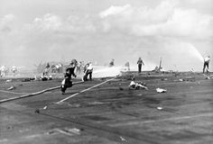 Aftermath of the November 25, 1943 kamikaze attack against the USS Essex. Fire-fighters and scattered fragments of the Japanese aircraft cover the flight deck. The plane struck the port edge of the flight deck, landing among planes fueled for takeoff, causing extensive damage, killing 15, and wounding 44.