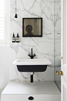 Hecker Guthrie - bathrooms - black and white sink, wall mounted sink, cast iron sink, art over sink, marble slab wall, paneled door, white p...