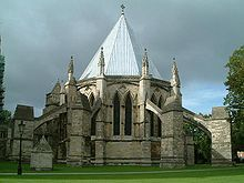 An external view of the Chapter House at Lincoln against a dark cloudy sky. The polygonal building has a steeply pointed lead roof, paired pointed windows and huge flying buttresses with splay out all around the building like spider's legs.