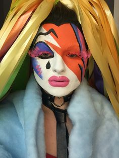 Club kid drag queen David Bowie inspired face makeup lightening bolt orange white pink blue with multicoloured ribbon hair. Lacey Lou
