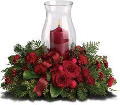 Abeto nobre perfumado e eucalipto semeado são o pano de fundo verde para rosas vermelhas, cravos vermelhos, bagas vermelhas e enfeites vermelho-foscos de Natal. Um recipiente de vidro abriga uma vela vermelha, enquanto fita vermelha com fio acrescenta um toque festivo ao acabamento.  Fotografai: Teleflora.com.
