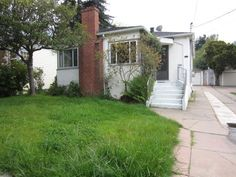 With overgrown landscaping and a disappear-into-the-background white paint color, this California bungalow was generally considered one of the least attractive homes on the block. Narrow, winding stairs and an overgrown trumpet vine and small tree that block the front door add to the home's uncared-for look.