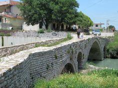 The Velabisht Bridge crosses a small tributary of the Osum River near Berat, Albania. Albania, Crosses, Bridge, Sidewalk, Southern, River, Rivers, Pavement, Legs