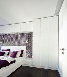 Zabudowa w sypialni w postaci białych szaf i pawlaczy bez uchwytów, otwieranych na dotyk - tip-on.