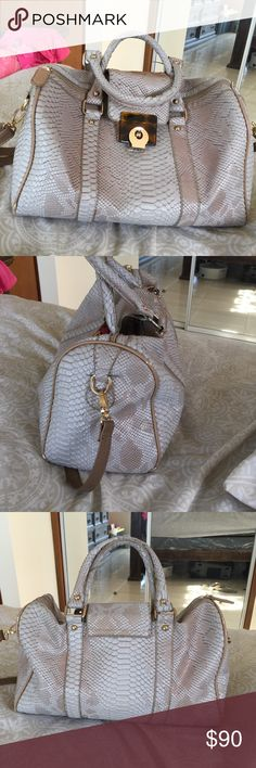 Faux snakeskin small duffle handbag. Preowned top zipper bag with double handles and shoulder strap. Satin animal print and paisley interior lining. Zipper pocket and two smaller pockets inside. Bag has strap clasp on outside also. Very sturdy bag. Few signs of wear. Galian New York Bags Satchels