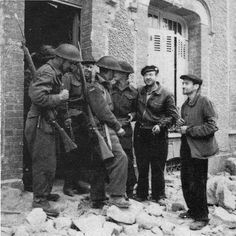 Civilians and soldiers on a sidewalk full of debris; Caen, July 1944
