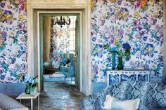 Giant print chintz wallpaper clashed with snakeskin print armchair, striped and dogtooth.
