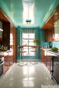 In the kitchen of a New York apartment designed by Philip Gorrivan, iridescent mosaic tiles and a ceiling lacquered in Benjamin Moore's Oceanic Teal pick up a color from the wallpaper in the hallway. Thonet barstools by York Street Studio. Roman shades in Homer wool in Verdigris by Gorrivan by Highland Court.