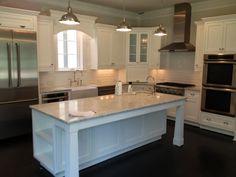 White on White Kitchen.  White Carrara Marble tops. Beveled white subway tile on the back splash