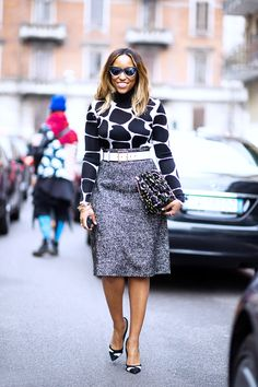 A black and white printed turtleneck is paired with a tweed skirt, white belt, printed clutch, and sunglasses