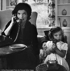 Mommy's girl: Jackie Kennedy on talks on the telephone as her young daughter Caroline mimics her on a toy phone, at their home in Hyannis Port, MA