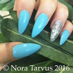 Pastel blue and silver glitter pointy, sharp stiletto nails. These nails acrylic ones decorated with some gel polish.