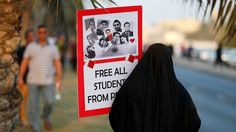 """An anti-government protester holds up a sign with photos of students detainees that read, """"Free All Students from Prison"""" as she walks to the female area during a rally organized by Bahrain's main opposition party Al Wefaq on Budaiya highway west of Manama, August 23, 3013.(Reuters / Hamad I Mohammed)"""