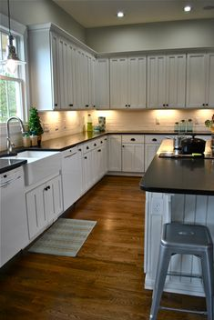 White cabinets and light walls. Dark countertops.