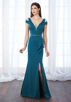 Sleeveless crepe trumpet gown with deep V-neckline featuring an illusion modesty panel, cutout cold shoulders, V-back, hand-beaded natural waistline finished with side ruffle accent, side slit, sweep train. Matching shawl included.