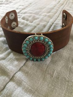 At 1.5 x 9.5 this is a beautiful Java Brown hand stained leather cuff. Hand stitched to the cuff is a stunning silver pendant with a dark red marbled center stone, rimmed with with smaller turquoise stones. With two clasp choices, it ensures the perfect fit for anybody.