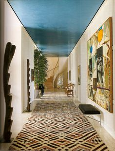 """The entry hall, which features one of our custom plasters in tropical cobalt on the ceiling, is a dramatic focal point of the home and was included to """"emulate the sky and ocean""""."""
