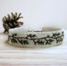 Pine branches circle this hand embroidered cuff bracelet, hand stitched on white linen with a lobster clasp and finished with a wee tassel.    Size:  I