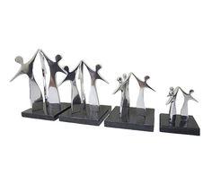 Troféu Equipe Peça: tridimensional, disponível em 4 tamanhos: 10 cm de altura, base 9x9x3cm. 13 cm de altura, base 11x11x3cm. 17 cm de altura, base 12x12x3cm. 21,5 cm de altura, base 13x13x3cm. Materiais disponíveis: alumínio (prata) ou bronze (dourado ou patinado). Base: madeira natural ipê ou madeira revestida de fórmica preta. Placa cortesia: aço inox (prata) ou latão (dourada), 7x2cm.