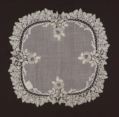 A wedding handkerchief, sheer white linen with rounded outline, border of bobbin lace with insert of bobbin lace in shape of stylized rose in center of each of four sides.