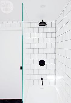 Gorgeous black bathroom fixtures seize the spotlight against an explosion of six-inch-square white tiles. Emphasized by contrasting dark grout, the wall tiles lend drama and make a statement in these snug quarters.   Image: Janis Nicolay   #ShowerGoals #Bathroom #WhiteInterior #StyleAtHome