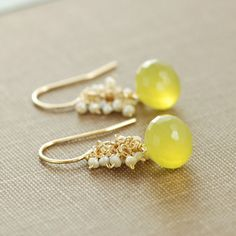 Plump yellow chalcedony briolettes are topped with clusters of lustrous seed pearls meticulously wire wrapped with handmade 14k gold filled headpins. A warm and sunny color combination, lovely for spring. Total earring length- 1 1/8 inches (2.8 cm) Chalcedony briolettes- 7 mm x 7 mm See more~ Gold earrings- http://www.etsy.com/shop/aubepine?section_id=6307607 Silver earrings- http://www.etsy.com/shop/aubepine?section_id=6718998 The rest of my jewelry shop- http://aubepine.etsy.com…