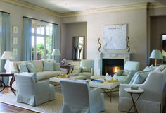 Hang gorgeous chandelier over coffee table, install a larger mirror over fireplace to reflect chandelier, and flank it with over sized abstract art. Have lots of ambient light around the room.