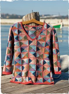 Designed by Kaffe Fassett, this gorgeous pullover is masterfully art knit in a colorful patchwork reminiscent of nautical flags. Handloomed in tweeded pima yarns that shift from persimmon, blush and copper to sky, indigo, lilac and olive. Classically fit and detailed with a v-neck, ¾-sleeves and handcrocheted trim.