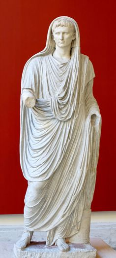 Augustus as Pontifex Maximus: head covered, wearing the toga and calcei patricii (shoes reserved for Patricians), he extends his right arm to pour a libation; a cupsa (container for officiel documents) lies at his feet. Greek marble (arms and head) and Italic marble (body), Roman artwork of the late Augustan period. Dates to between circa 90 and circa 100 AD.  Courtesy & currently located at the National Museum of Rome.