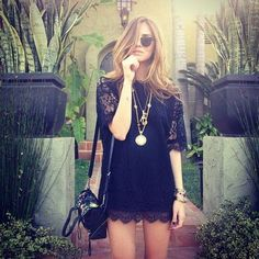 Short Black lace dress with gold jewelry.