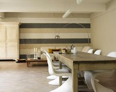 Una pared de rayas anchas en tonos cálidos neutros llama la atención.