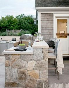 The backsplash is beefed up with a counter to serve as a bar area, where guests can sit and chat with the cook. Fieldstone and granite from Connecticut Stone Supply.   - HouseBeautiful.com