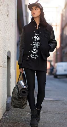 All black everything. Varsity jacket gives it some edge while the yoga mat let us know she can get zen.
