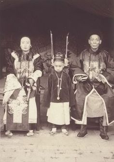 """""""A Manchu official and presumably his wife and son. Others have reported this scene (erroneously, IMHO) as """"Wedding photo of the late Qing Dynasty."""" If so, the bride would be veiled and we would never see her face, nor would there be the existence of a son yet. The woman is wearing a Single Tooth pedestal shoe and did not bind her feet; that means she was Manchu. Since Manchu could not intermarry with Han, that meant her husband too was Manchu. Hence, a Manchu family portrait, IMHO."""""""