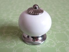 Porcelain Knobs Dresser Knob Drawer Knobs Pulls Handles White Ceramic Silver Kitchen Cabinet Knobs / Furniture Knob Handle Pull Hardware Material: ceramic and zinc alloy Color: white and silver  Measurement: Dia: 1 1/4 (32mm) Dia of basement: 1.1 (27 mm) When installed the knob sticks out 1 1/2 (40mm)  One screw is included, 1 (25mm) long.   Please visit my shop for more knobs and pulls: http://www.etsy.com/shop/LynnsHardware