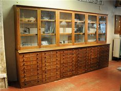 Antique Oak Cabinet (from ex museum) with many shallow drawers and glassed in shelving above. Could be great for storing small craft supplies for beads, threads, and paper crafting supplies below and other tools/fibers/fabrics above.