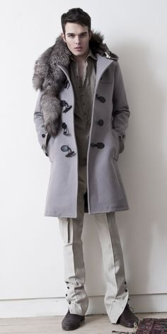 Waverly Hills Industrial felt duffle coat w/ horn toggle closure, blue tundra fox scarf, cotton metal tunic w/ elongated tie up sleeve and side buckle detail, slim cut cargo pant w/side button closure on legs.   By: Theodore Alexander