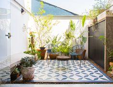 Área externa de casinha tem piso estampado, banco de concreto e muitas plantas.
