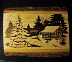 ONE OF A KIND HAND CRAFTED PYROGRAPHIC WOOD BURNED PLANK PLAQUE    Wood Burned, Pyrographic winter scenery of a snowy log cabin with wood smoke rolling out of the stone chimney, surrounded by pine trees Original Art Work by Artist Valerie Mason    PLANK PLAQUE IS 11 INCHES WIDE X 9 INCHES LENGTH X 1/2 INCH THICK    All wood burning art is sealed 5 coats of clear high gloss polyurethane