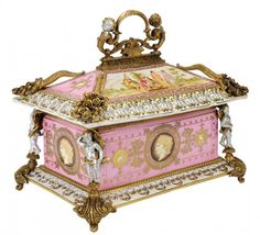 A ROYAL VIENNA STYLE PORCELAIN CASKET WITH BRONZE MOUNTSEarly 20th Century The arched handle above a rectangular coffer top decorated with Classical scenes, with cornucopias at corners, over a rectangular case decorated with cameo medallions, with putti-form terms, on acanthus cast feet. Blue beehive overglaze mark to underside.