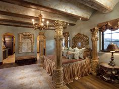 This ornate master bedroom features an elaborate four poster bed resembling Roman columns that stretch up toward intricately painted ceiling beams.  A gold detailed headboard matches the look while an equally ornate bedside lamp, nightstand, and gold-detailed artwork complete the rich texture of this space.