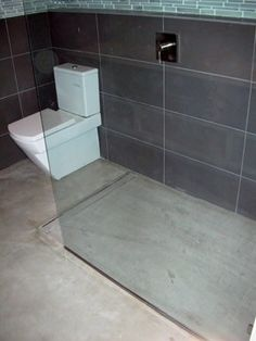 concrete floor. The large tile in shower. Walls subway tile.