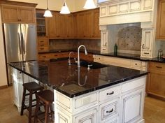 Titanium schist kitchen island with white cabinet. oak cabinets for the perimeter.  Visit globalgranite.com for your natural stone needs.