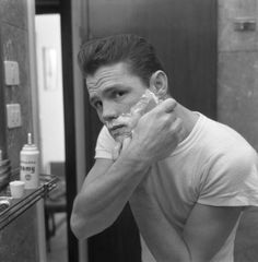 American jazz musician Chet Baker, reflected in a mirror while shaving, Lucca 1961.