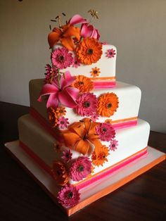 Gerbera daisies and lilies adorn this summer wedding cake in pink and orange. Carrot cake with cream cheese filling makes this a deliscious choice for any wedding. Each sugar flower is handcrafted in every little detail.